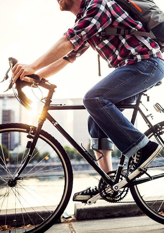 Wyjaśnienie stanu zapalnego - mężczyzna z bordą w koszuli w kratę jedzie na rowerze