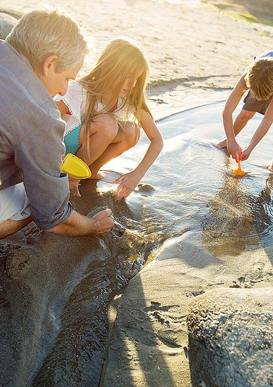 Odkryj radość płynącą z ruchu - ojciec z dziećmi bawią się łopatkami na plaży