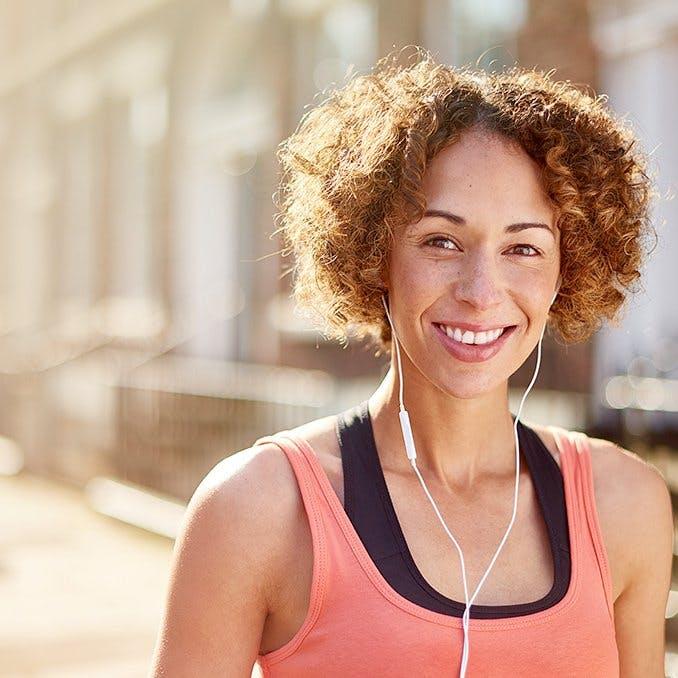 Ruchy pomagające złagodzić ból pleców - uśmiechająca się kobieta idąca ulicą