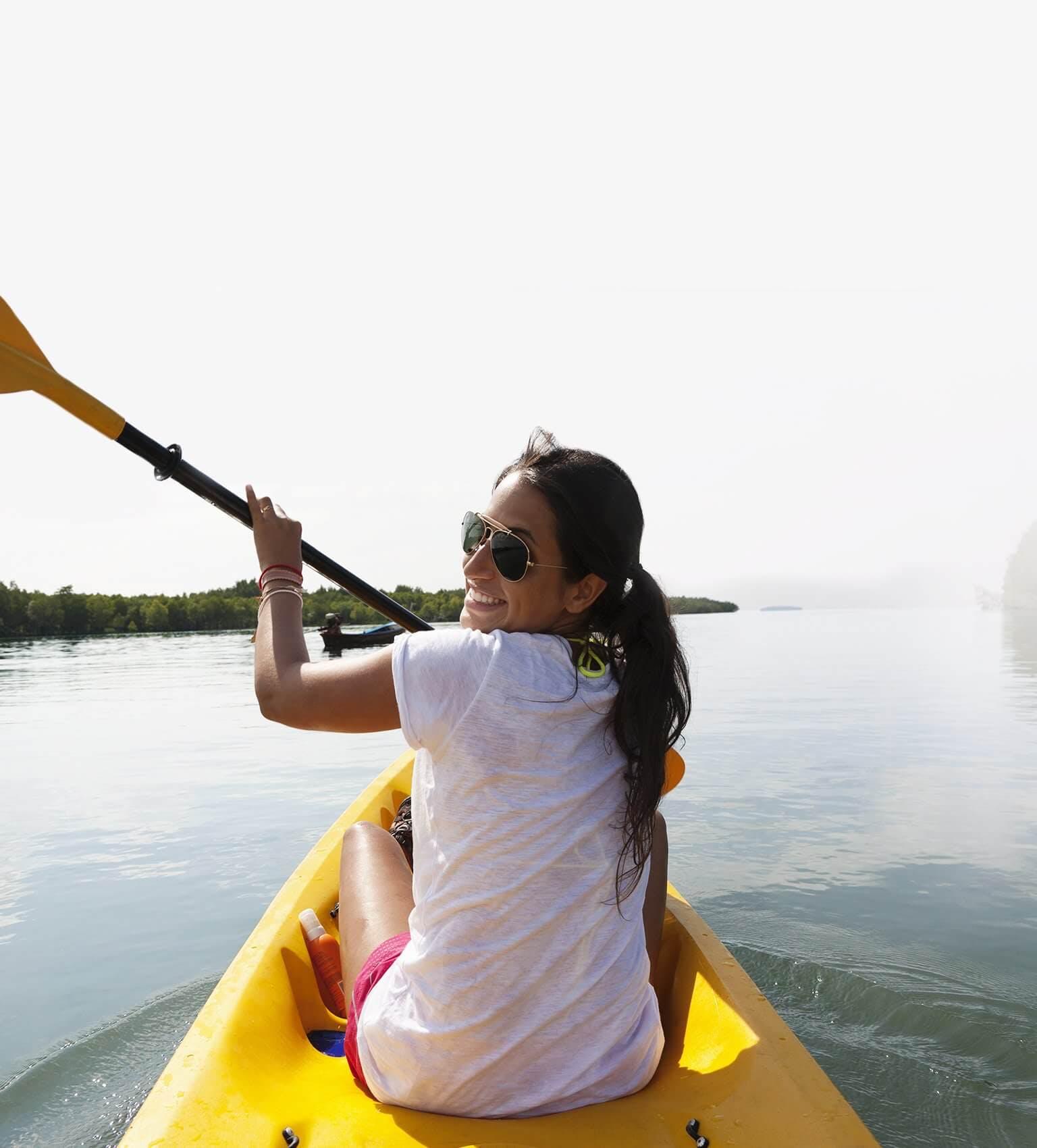 Uśmiechnięta dziewczyna w okularach przeciwsłonecznych płynąca na kajaku przez jezioro