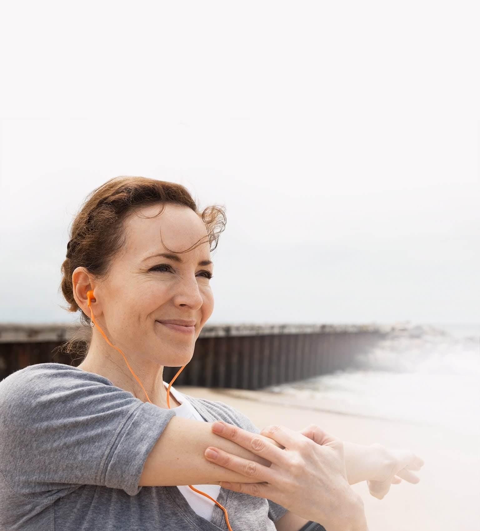 Kobieta przeciągająca się na plaży, łapiąca się za przedramię