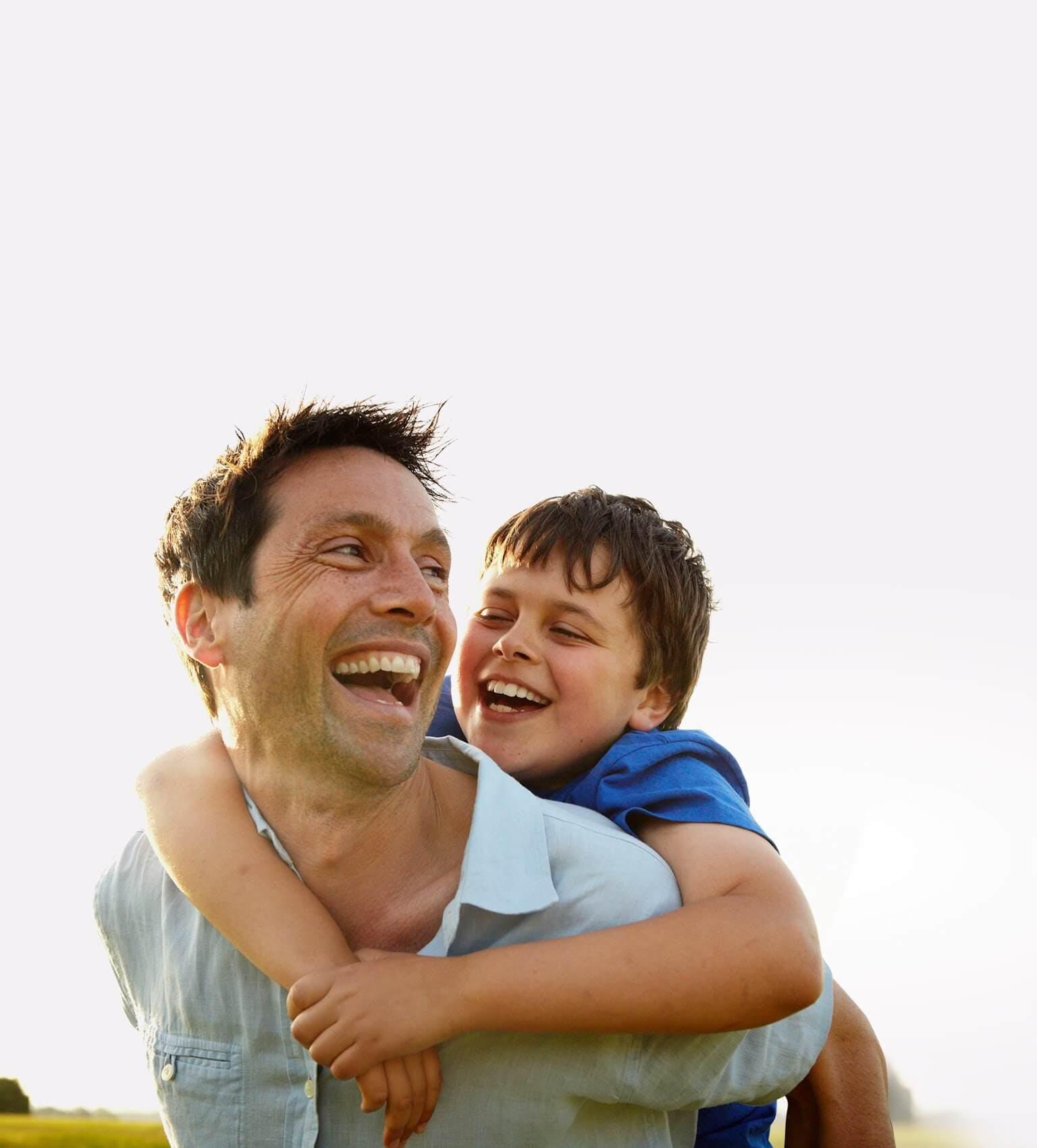 Uśmiechnięty ojciec trzymający na plecach swojego zadowolonego syna