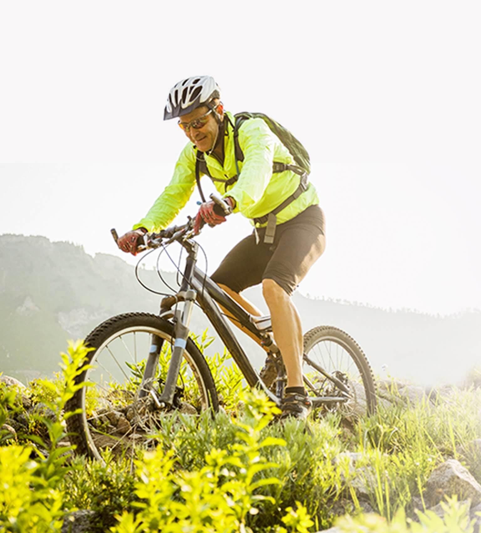 Mężczyzna na rowerze górskim w scenerii gór i łąki
