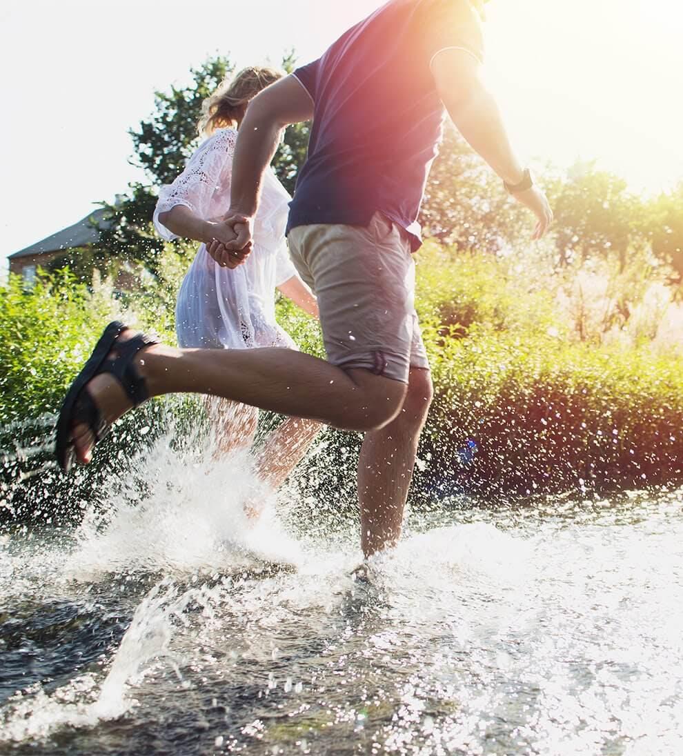 Para trzymająca się za ręce, biegnąca przez strumień