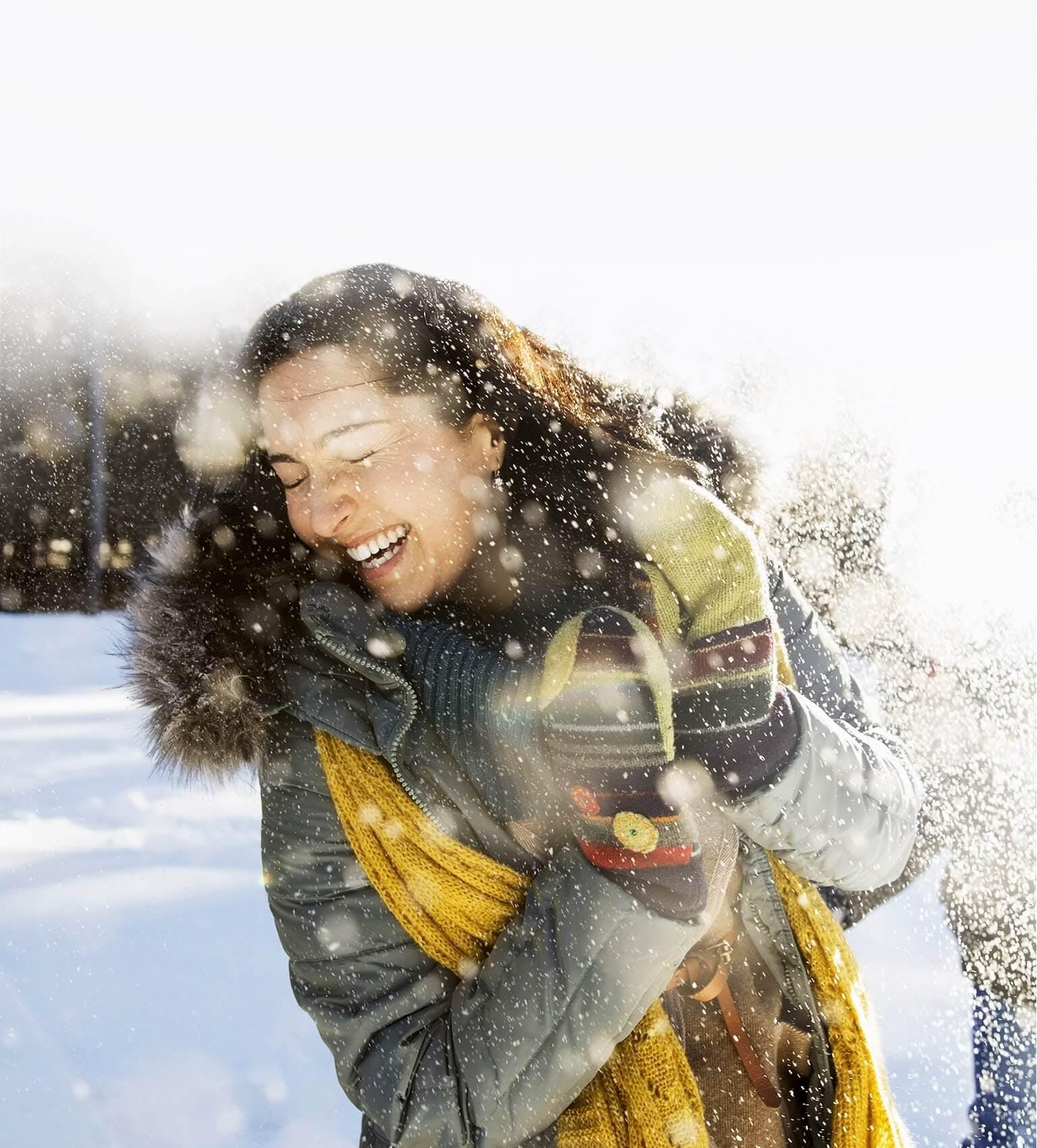 Uśmiechnięta, ciepło ubrana kobieta w zimowej scenerii