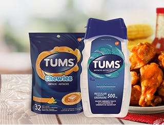 Bag of Tums Chewies & a bottle of Tums Regular Strength next to spicy chicken wings