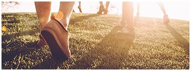 Close up of people's shoes exercising on a grass field