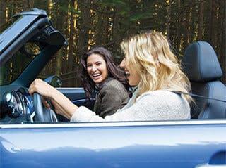 Dve ženy, ktoré idú autom a smejú sa