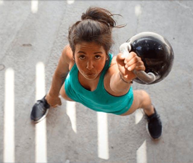 Dívka, která cvičí se závažím