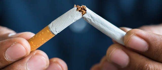 Pair of hands breaking a cigarette in half