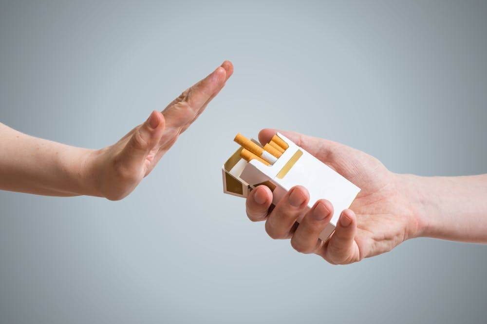 Hand refusing cigarette offer