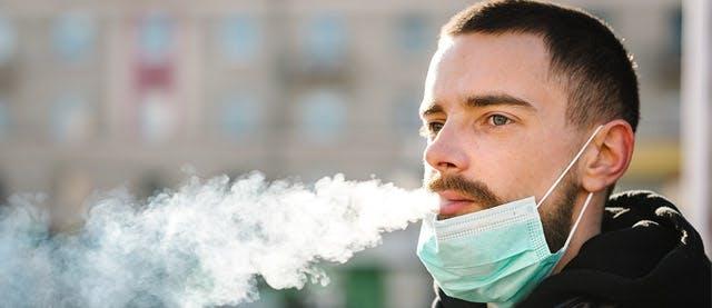 man with mask blowing smoke